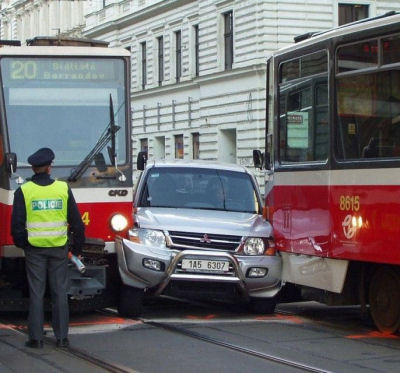 An image of a suv blocked between two trams.